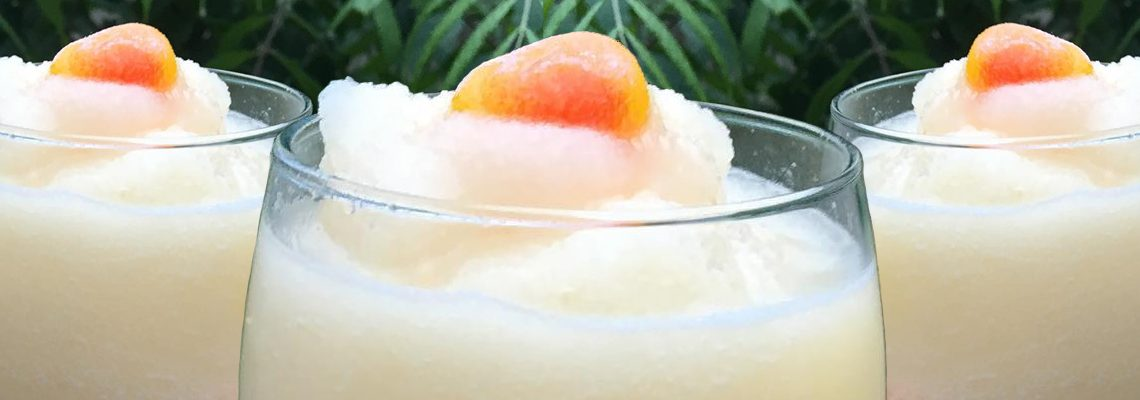 three glasses full of pale peach slush beverage with peach candies on top